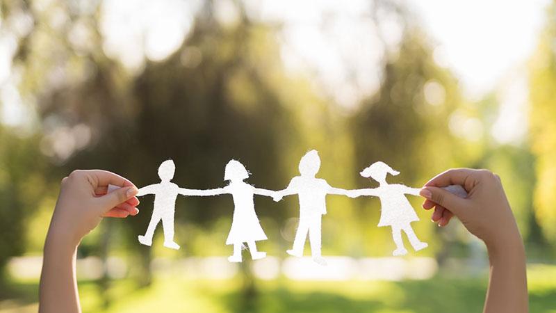 Lány papírból megrodmázott családját tartja a levegőben